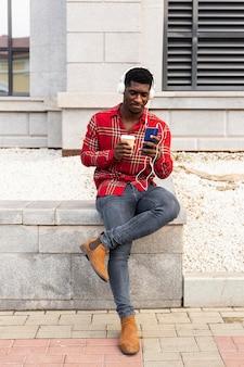 Длинный снимок человека, держащего мобильный телефон и кофе