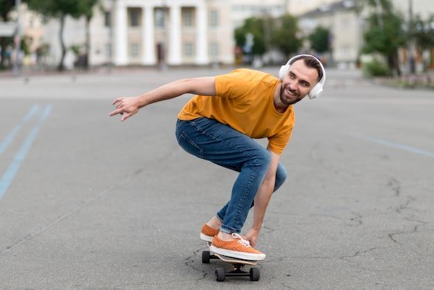 スケートボードを持つ男のロングショット