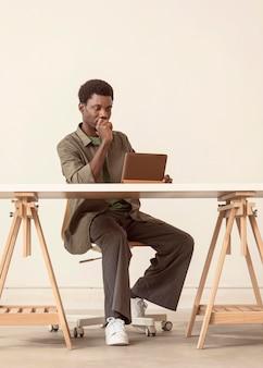 座ってラップトップで作業している人のロングショット