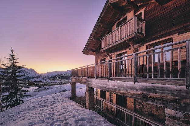 日の出時のフランスアルプスのアルプデュエズスキーリゾートのキャビンのファサードのロングショット