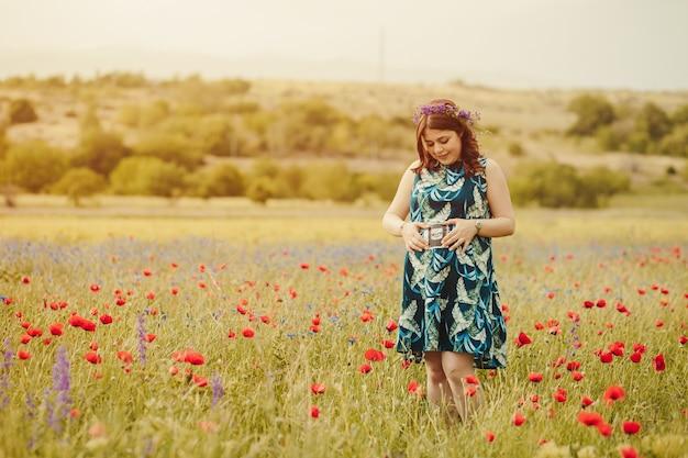 将来の赤ちゃんの超音波スキャン写真を保持している野生のポピーと花でいっぱいの牧草地で出産を楽しむ若い妊婦のロングショット