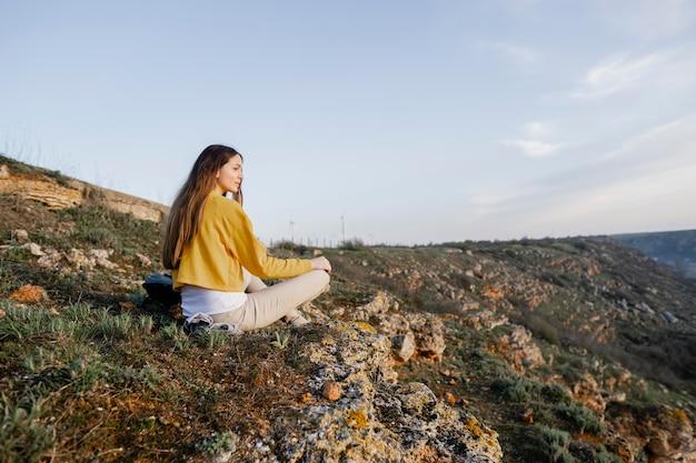 彼女の周りの自然を楽しんでいる若い女性のロングショット