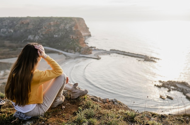 彼女の周りの自然を楽しんでいる若い女性のロングショット 無料写真