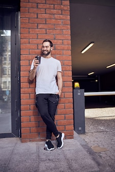 거리를 찾고 커피와 잘 생긴 남자의 긴 총 초상화