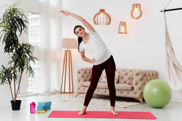 Long shot pregnant woman exercising on fitness mat