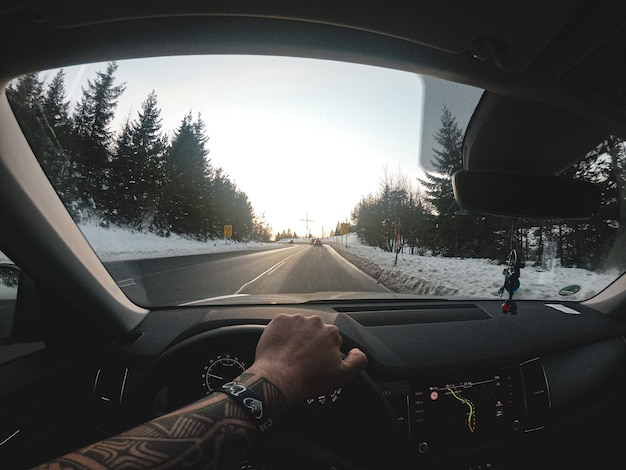 Long shot of a road cleared of snow. captured from inside a car