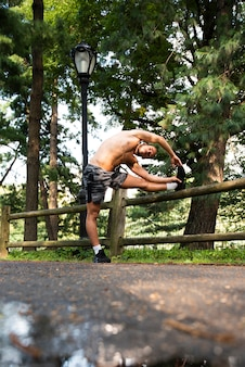 Long shot of runner stretching in park