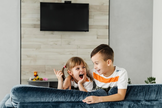 Long shot of siblings and television on the wall