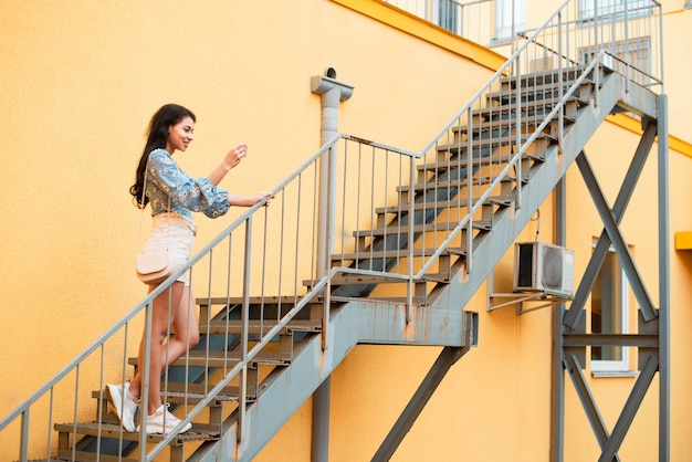 Long shot of sideways woman standing on stairs and taking photos