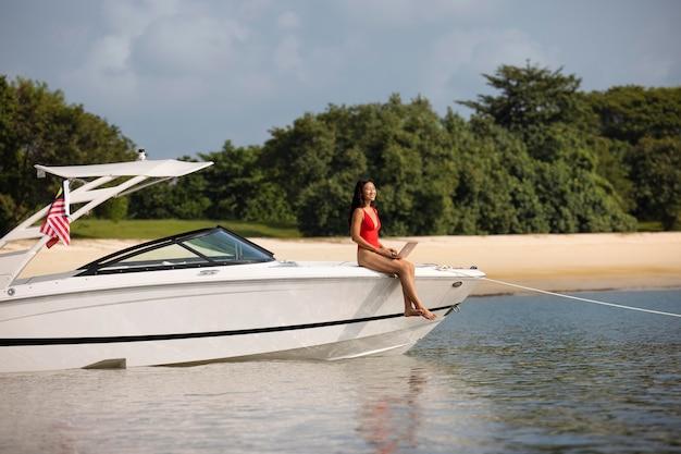 ボートにラップトップを持つロングショットスマイリー女性