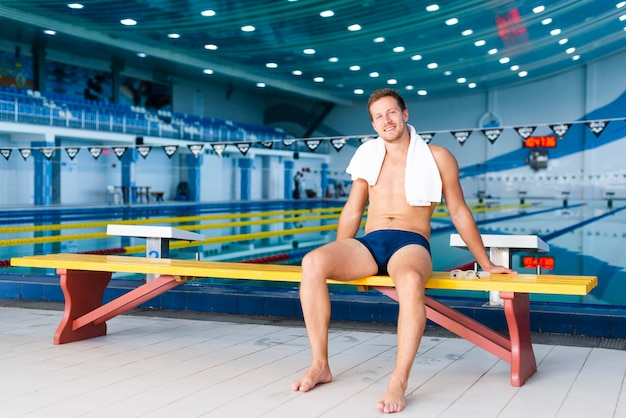 Long-shot swimmer posing with towel on his shoulders