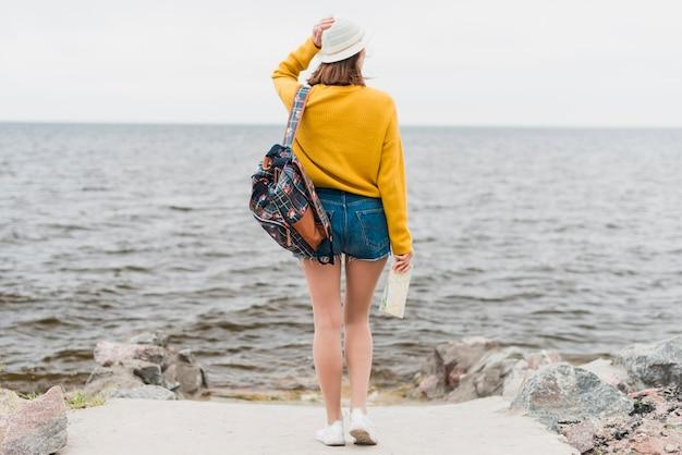 Long shot of traveler facing the sea