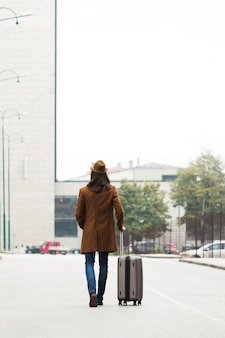 Long shot traveler with coat and luggage