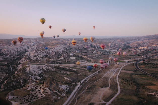 Long shot of various multi-colored hot air balloons floating in the sky