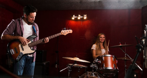 Long shot view of woman playing drums and man playing guitar