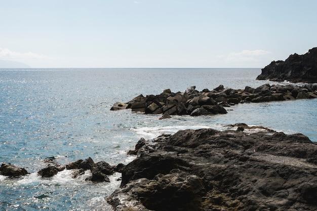 Long shot wavy water at rocky shore