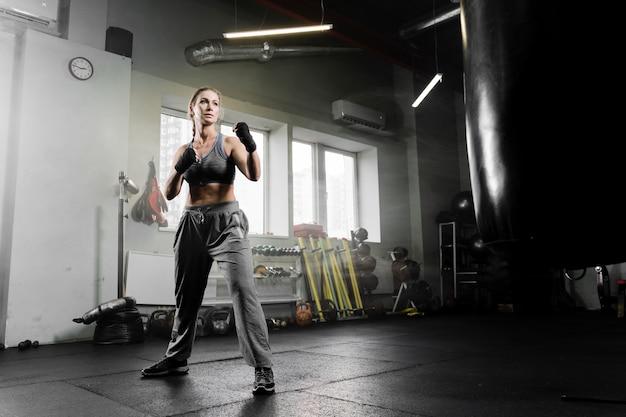 Long shot woman boxing in training center