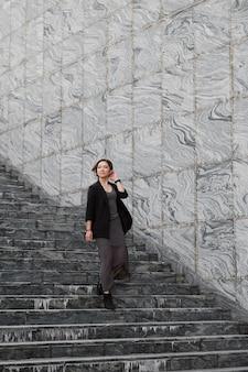 계단을 내려 오르는 롱 샷 여자