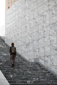 Long shot woman climbing up stairs