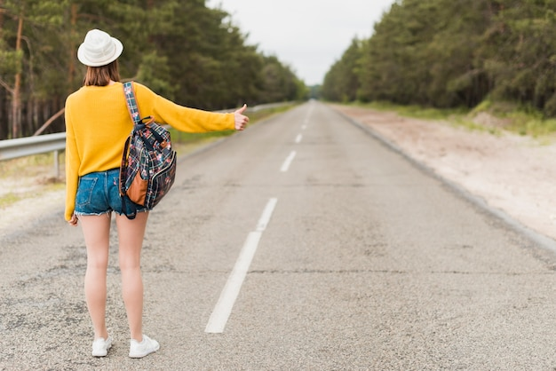 Long shot of woman hitchhiking