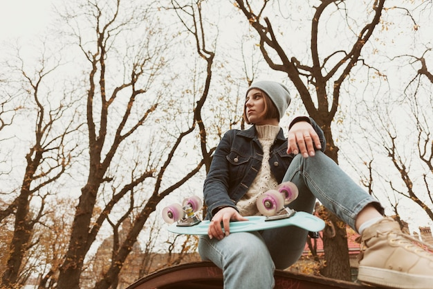 Donna del colpo lungo che tiene uno skateboard
