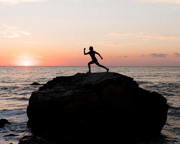 岩を引っ掻くスポーツウェアのロングショットの女性