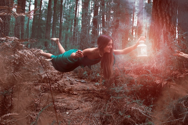 Long shot woman levitating in the forest with lantern