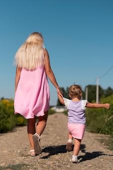Long shot of a woman and little girl walking
