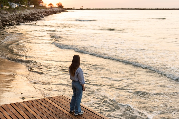 Long shot woman looking at the sea