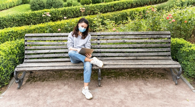 Long shot woman looking at a tablet while wearing medical mask