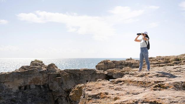 Long shot woman looking through binocular with copy space