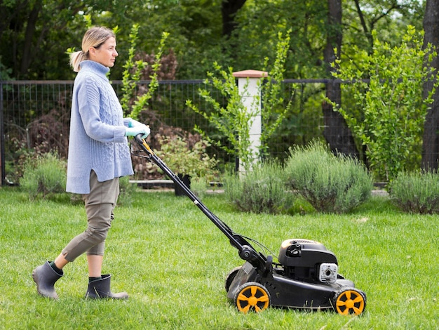 Long shot woman mowing the yard