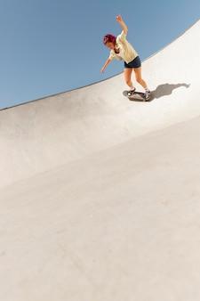屋外のスケートボードでロングショットの女性