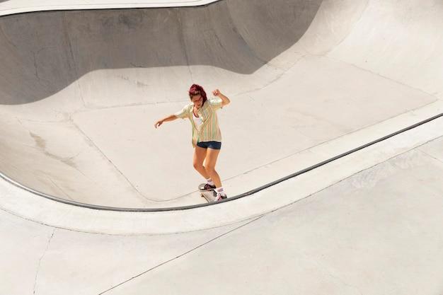 スケートボードのロングショットの女性