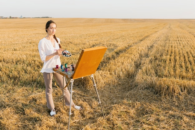Long shot woman painting in the nature