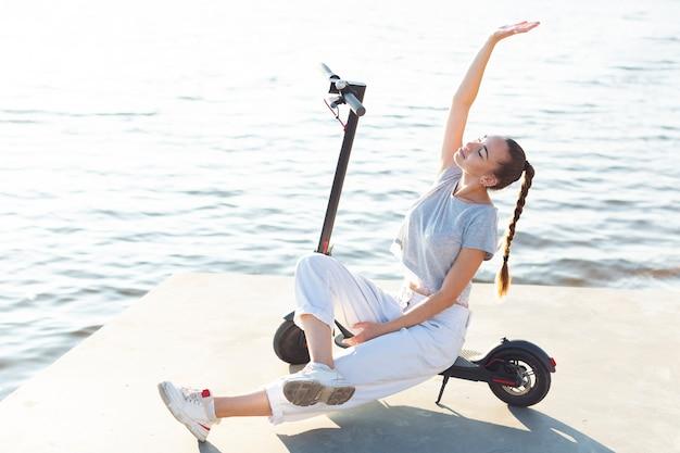 Длинный выстрел женщина позирует на скутере