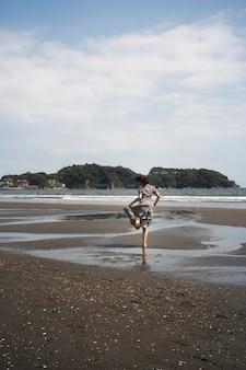 롱 샷 여자 해변에서 실행