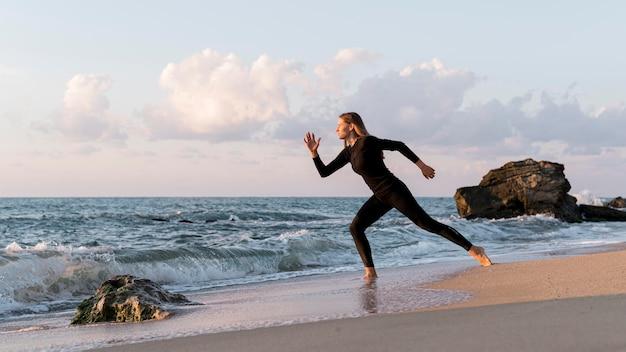 ビーチで走っているロングショットの女性