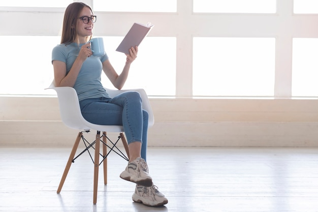 Long shot woman sitting on chair while reading a book