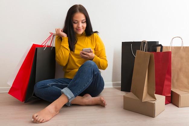 Long shot woman sitting next to shopping bags