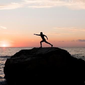 Donna del colpo lungo in abiti sportivi che graffiano su una roccia con lo spazio della copia
