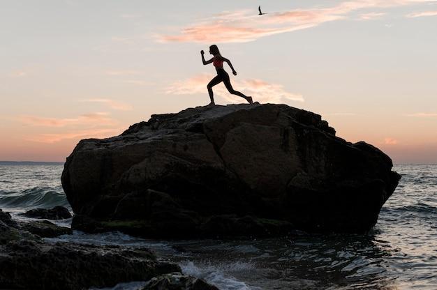 Colpo lungo donna in piedi in una posizione sportiva su una roccia