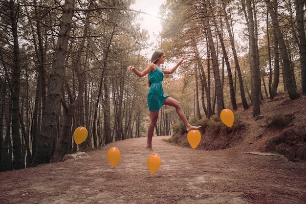 Long shot woman stepping on levitating balloons
