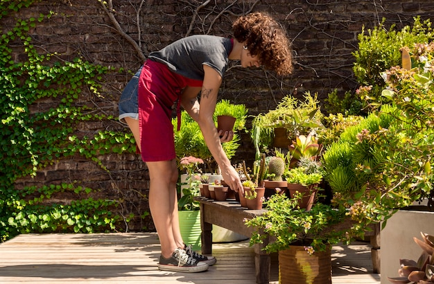 Long shot woman taking care of her plants