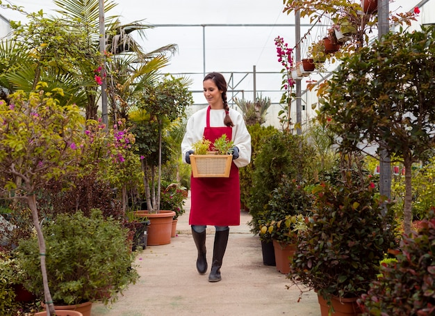Long shot woman wearing gardening clothes and holding basket in greenhouse