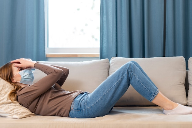 Long shot woman with mask staying on the couch