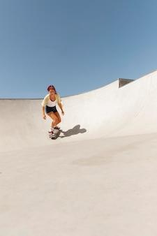 屋外でスケートボードを持つロングショットの女性