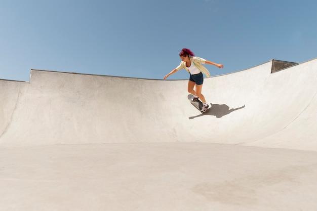 밖에 스케이트보드를 탄 롱샷 여자