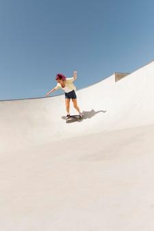 스케이트 보드와 함께 롱 샷 여자