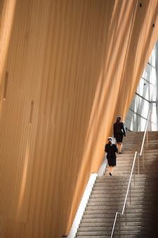 Long shot women climbing up stairs